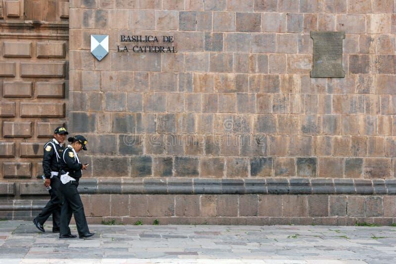 Police dans l'avant une façade d'église catholique dans Cuzco Pérou images libres de droits