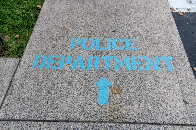 Sign on floor police. Police department sign spray painted on sidewalk in blue letters,, stencil type royalty free stock images