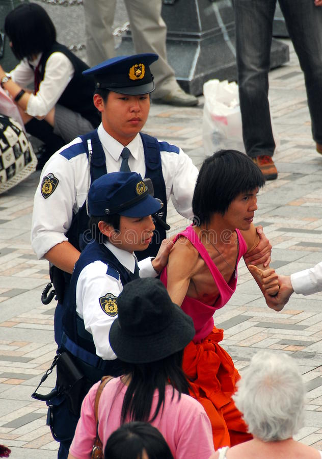 Police detaining man. Japanese police officers detaining a resisting young man for causing offence and public nuisance stock photo