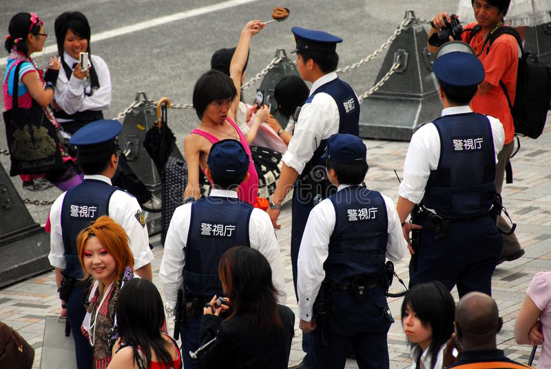 Police detaining man. Japanese police officers detaining a resisting young man for causing offence and public nuisance stock photos