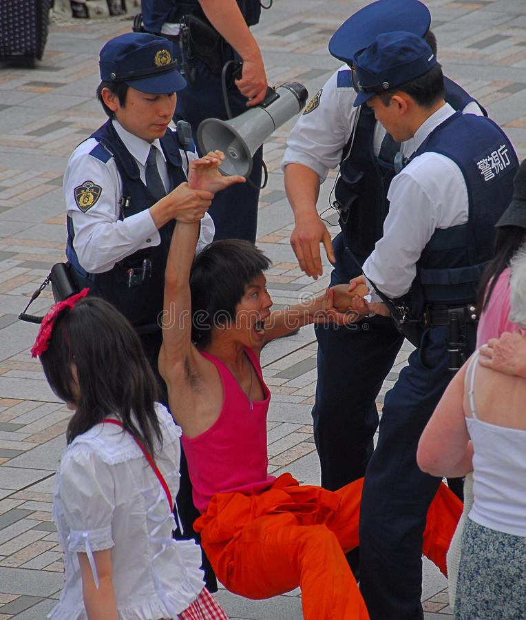 Police detaining man. Japanese police officers detaining a resisting young man for causing offence and public nuisance stock image