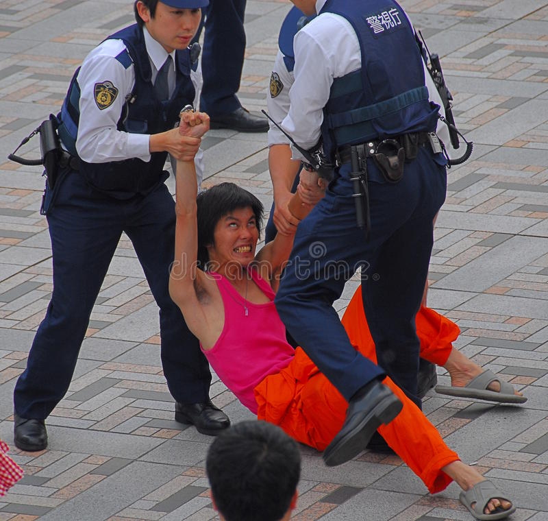 Police detaining man. Japanese police officers detaining a resisting young man for causing offence and public nuisance stock photography