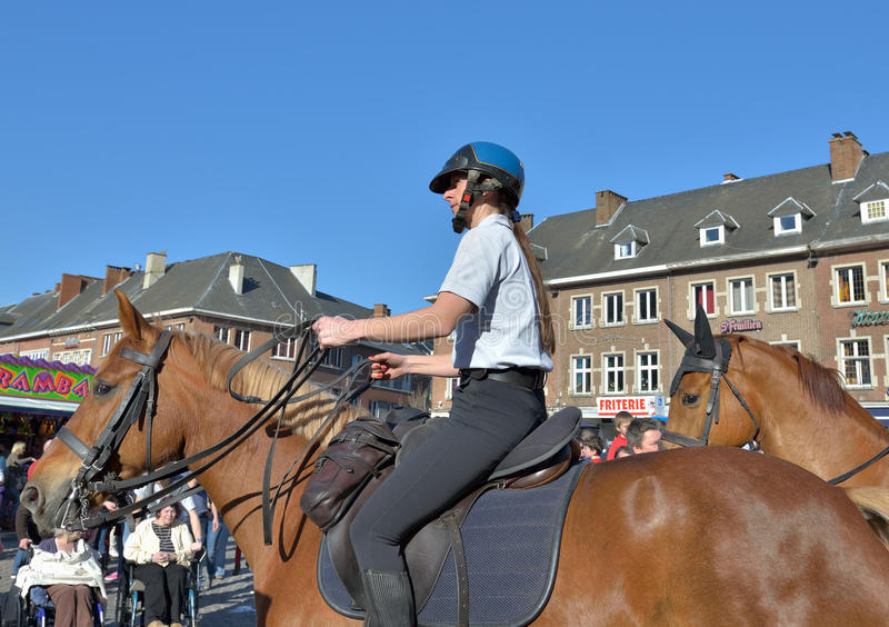 Police on duty during carnival in Nivelles, Belgium. NIVELLES, BELGIUM-MARCH 03, 2014: Police on horses protected public during yearly carnival in Nivelles stock photos