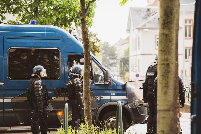 Police forces securing street in Strasbourg France Yellow Vests protest. Strasbourg, France - Apr 28, 2019: Side view of police officers near vans securing stock images