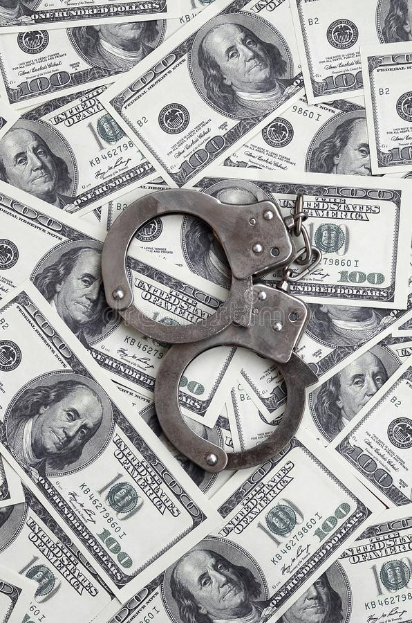 Police handcuffs lie on a lot of dollar bills. The concept of illegal possession of money, illegal transactions with US dollars. Economic Crime royalty free stock photos