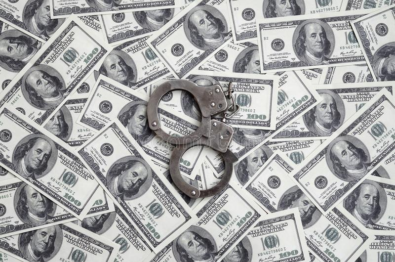 Police handcuffs lie on a lot of dollar bills. The concept of illegal possession of money, illegal transactions with US dollars. Economic Crime stock photo
