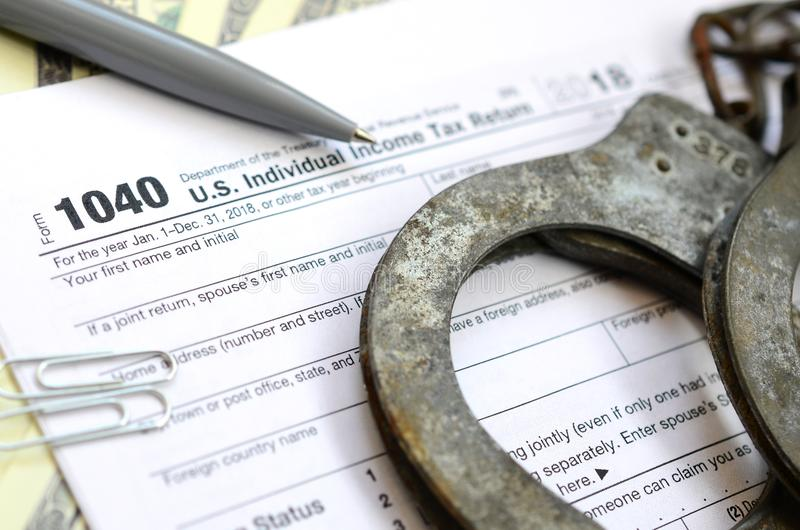 Police handcuffs lie on the tax form 1040. The concept of proble royalty free stock photography