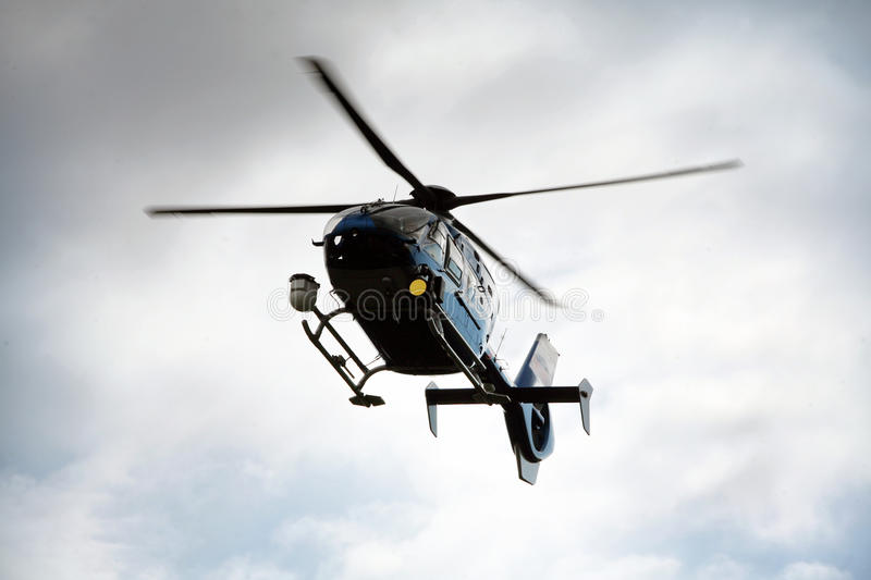 Police helicopter. Blue and silver police helicopter flying above stock photos