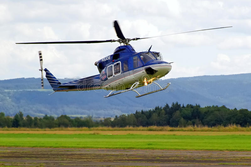 Police helicopter in flight. Scenic view of a police helicopter hovering over a field in the Czech Republic stock image