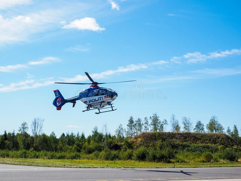 Police helicopter from norwegian authorities hoovering. Over landing field royalty free stock photos