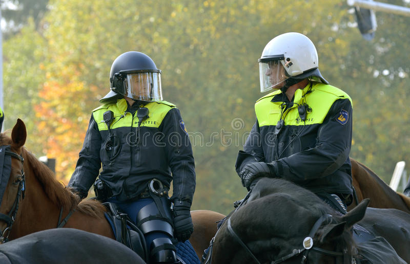 Police on horseback. ENSCHEDE, THE NETHERLANDS - OCT 31, 2015: Police on a horseback are having an eye for security during a demonstration stock photos