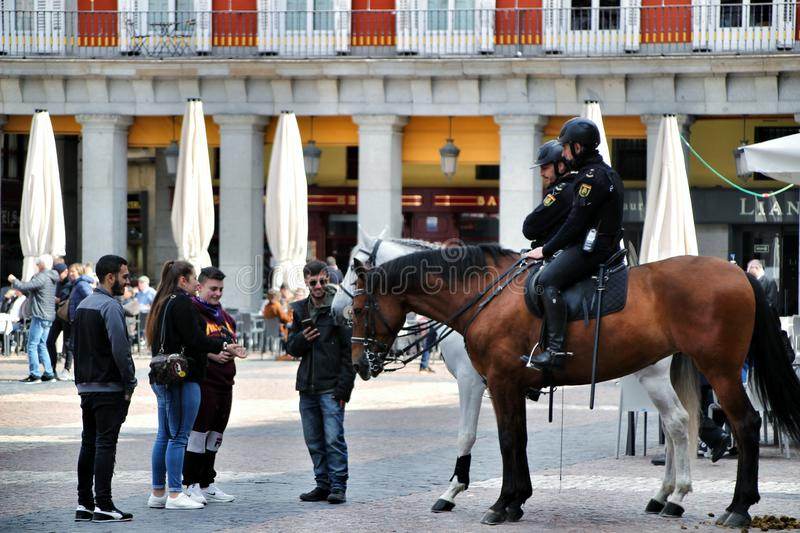 Police mounted on horseback watching the streets. Madrid, Spain- March 7, 2019: Police mounted on horseback and talking with people watching the streets of royalty free stock photo