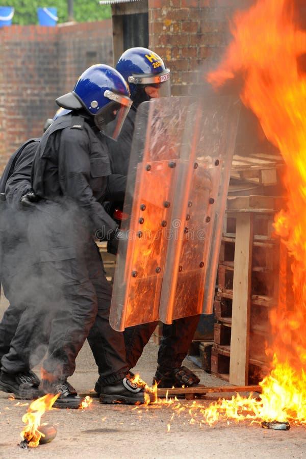 Police move through a burning barricade stock image