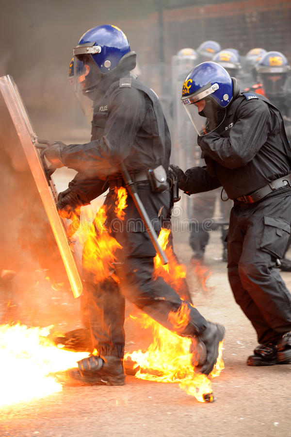 Police move through fire bombs stock photo
