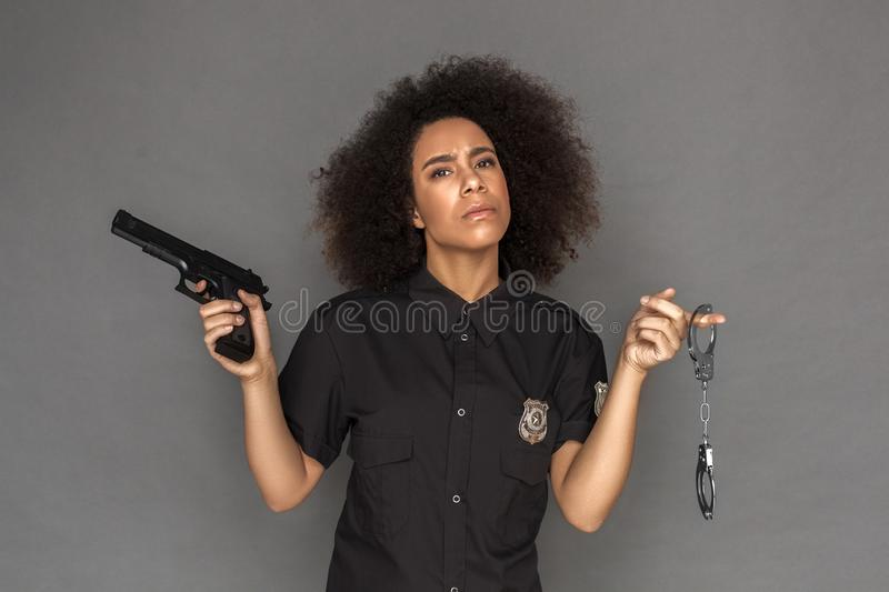 Police. Mulatto woman standing isolated on grey with gun and handcuffs serious stock image