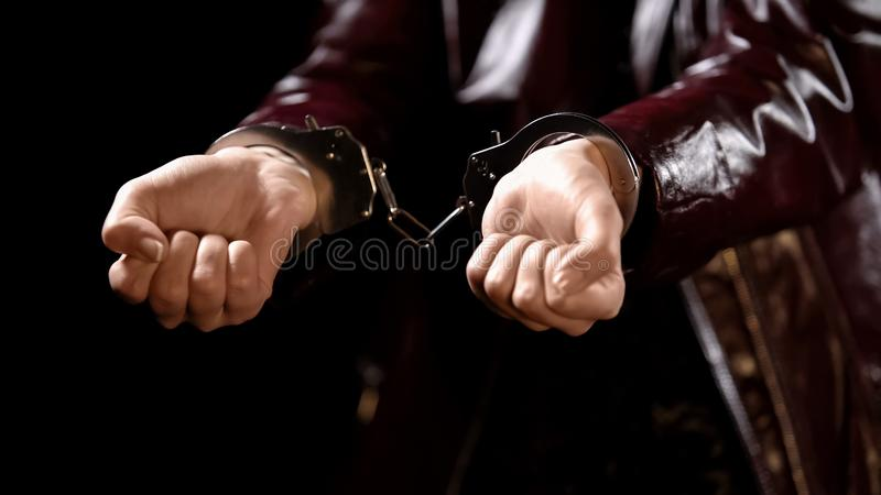 Police officer arrests young woman for prostitution, hands handcuffed close up royalty free stock photography