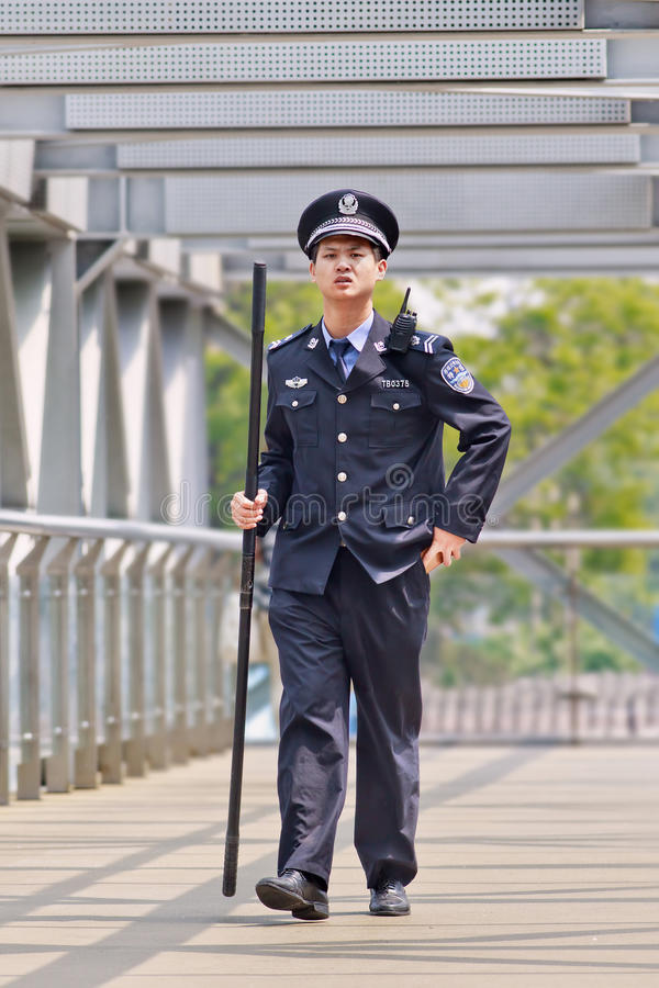 Police officer with a baton on pedestrian bridge, Beijing, China royalty free stock photography