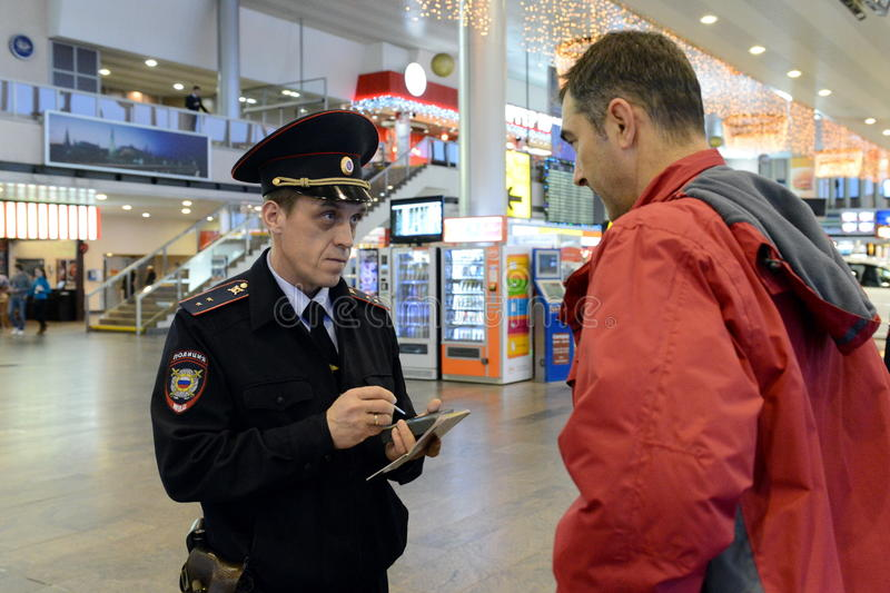 A police officer checks the citizen's information database at the entrance to the Moscow airport. stock photography