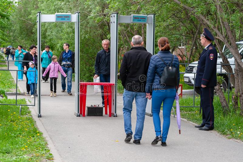 A police officer controls the passage of citizens through the metal detector frame, before entering the festive event. Surgut, Russia, 06.12.2019: A police royalty free stock images
