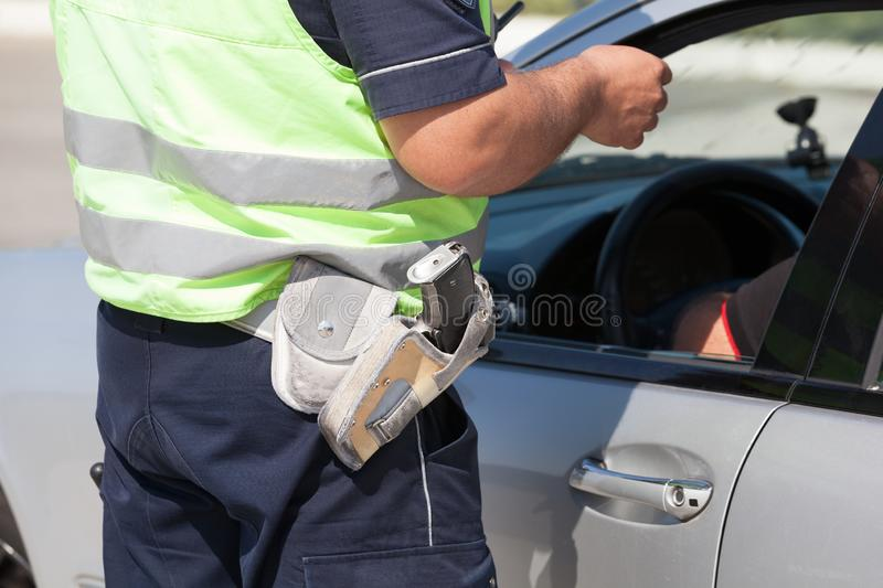 Police officer checking driving license of a car driver during traffic control royalty free stock images