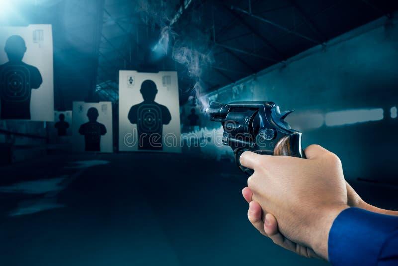 Police officer firing a gun at a shooting range / dramatic light royalty free stock image