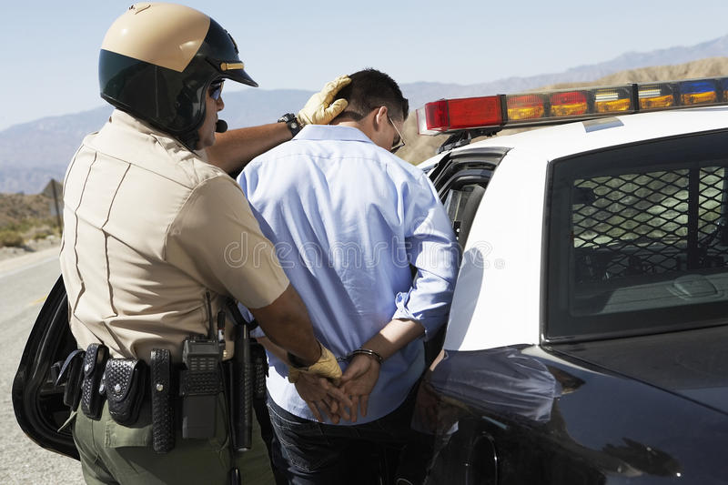 Police Officer Guiding Apprehended Man Into Police Car stock image