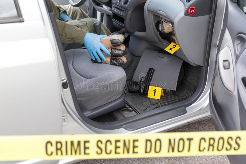 Police officer holding drug packages found in secret compartment. Policeman holding drug packages discovered in secret compartment of a car royalty free stock photo