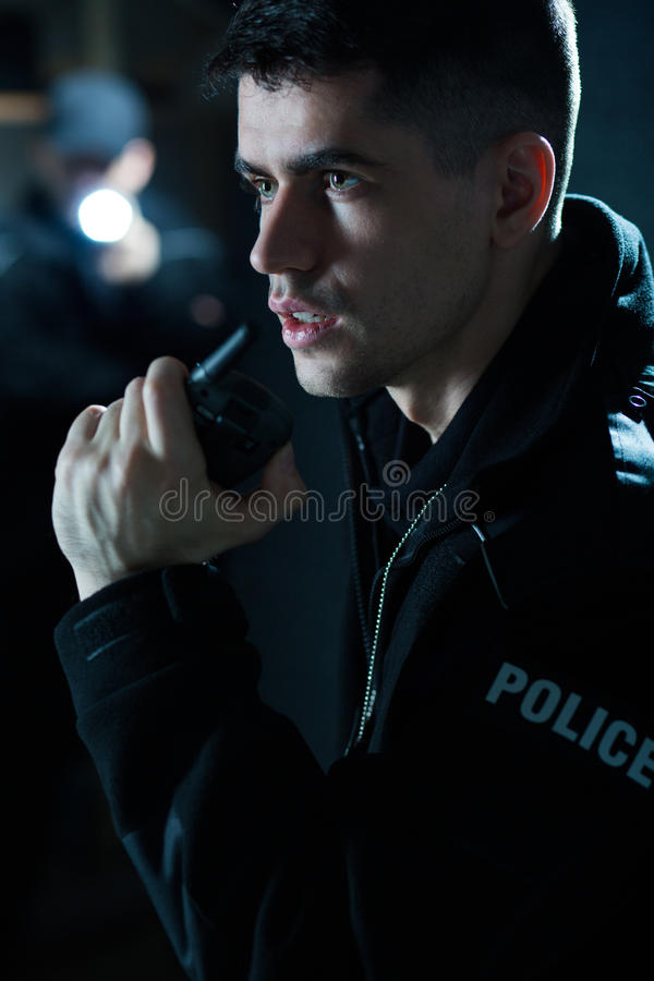 Police officer holding radio. Portrait of a young police officer holding radio royalty free stock photography