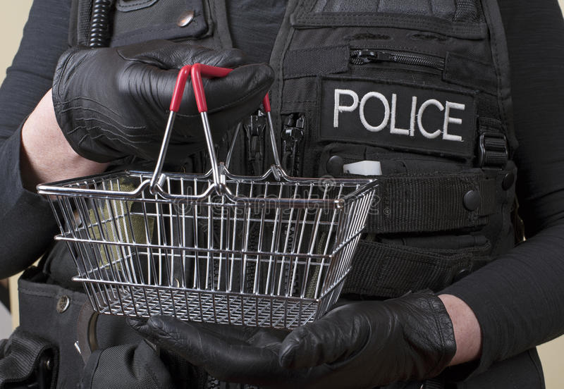 Police officer holding small wire basket stock photography