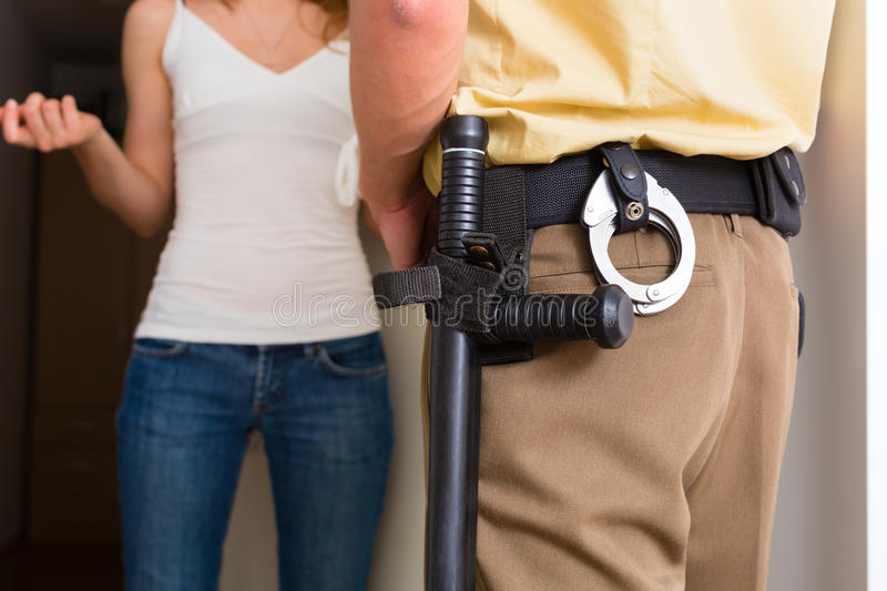 Police officer interrogation woman at front door stock images