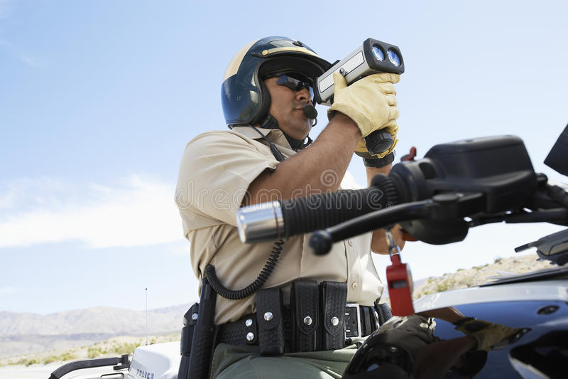Police Officer Looking Through Radar Gun royalty free stock photography
