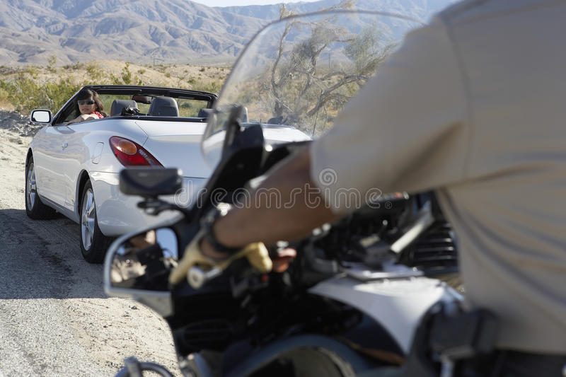 Download Police Officer On Motorbike Stopping Car On Desert Road Stock Photo - Image: 30842950