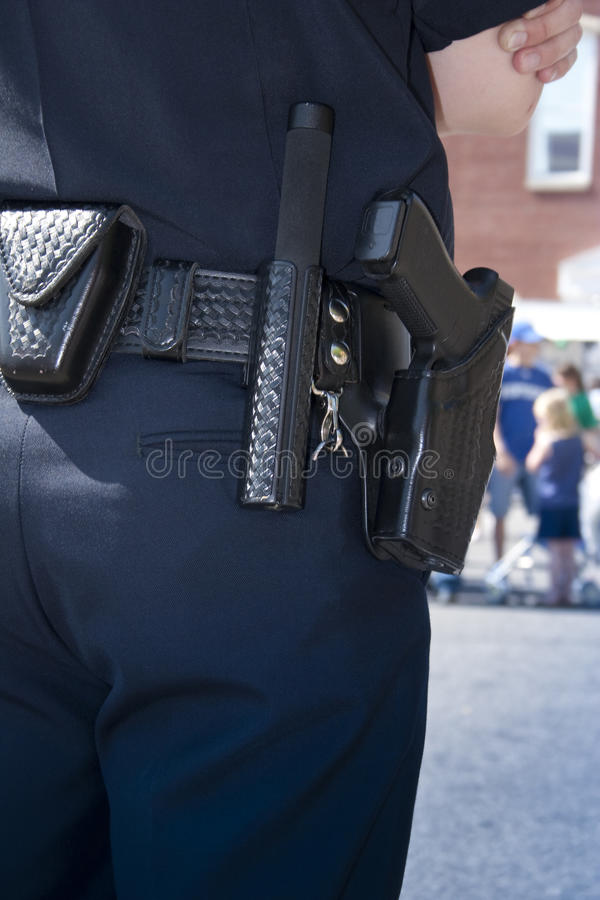 Police Officer Protecting. Closeup of a police officer, wearing a gun holster with a pistol and nightstick. Watching over crowd royalty free stock photo