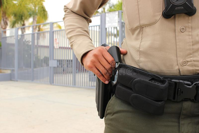 Police officer protecting high school campus. School security concept - armed police officer protecting a high school campus in California royalty free stock photo