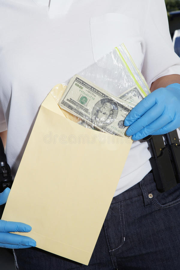 Police Officer Putting Money In Evidence Envelope. Midsection of a police officer putting money in evidence envelope royalty free stock images