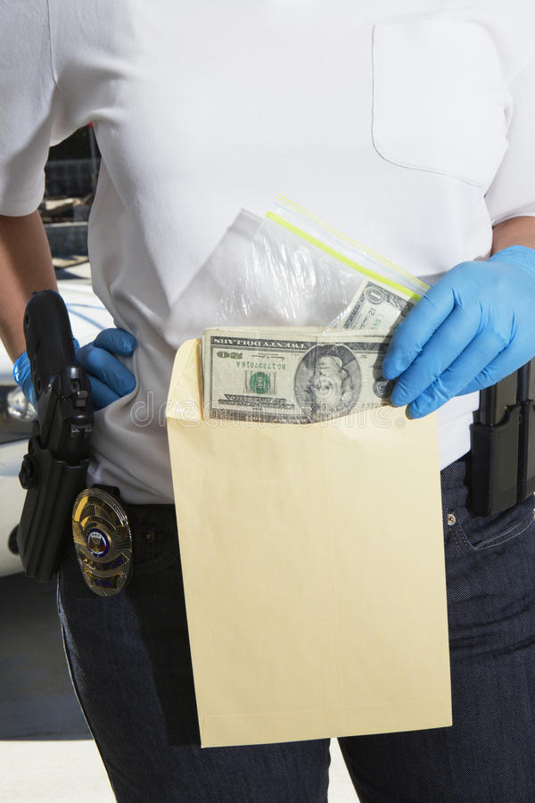 Police Officer Putting Money In Evidence Envelope. Midsection of a female police officer putting money in evidence envelope stock photos