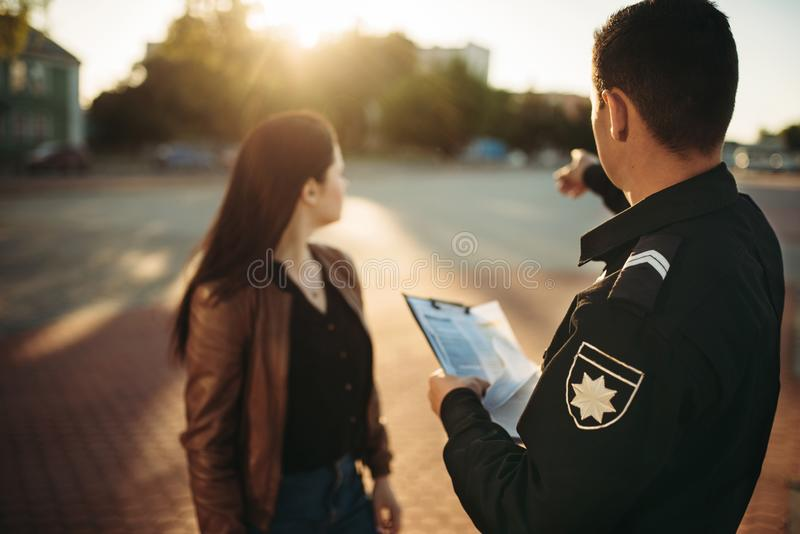 Police officer shows parking place to driver. Police officer in uniform shows parking place to female driver. Law protection, car traffic inspector, safety royalty free stock photos