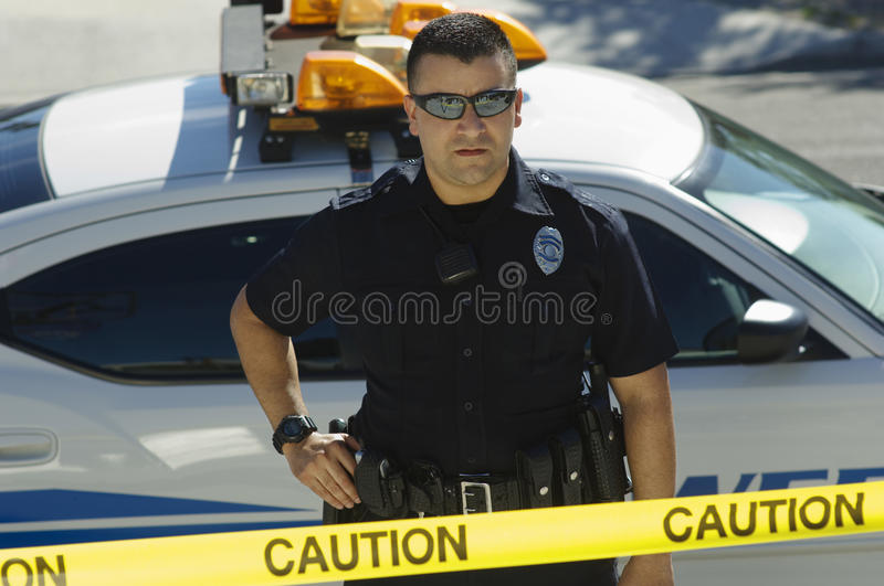 Police Officer Standing Behind Caution Tape royalty free stock images