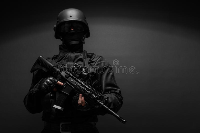 Police officer with weapons. Spec ops police officer SWAT in black uniform studio royalty free stock photos