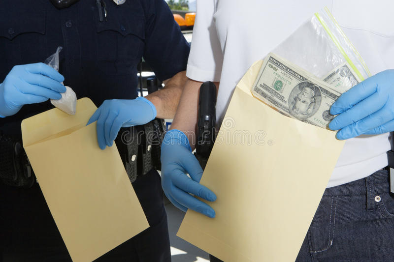Police Officers With Evidence Envelopes. Midsection of two police officers putting dollars and drug packet in evidence envelopes stock image