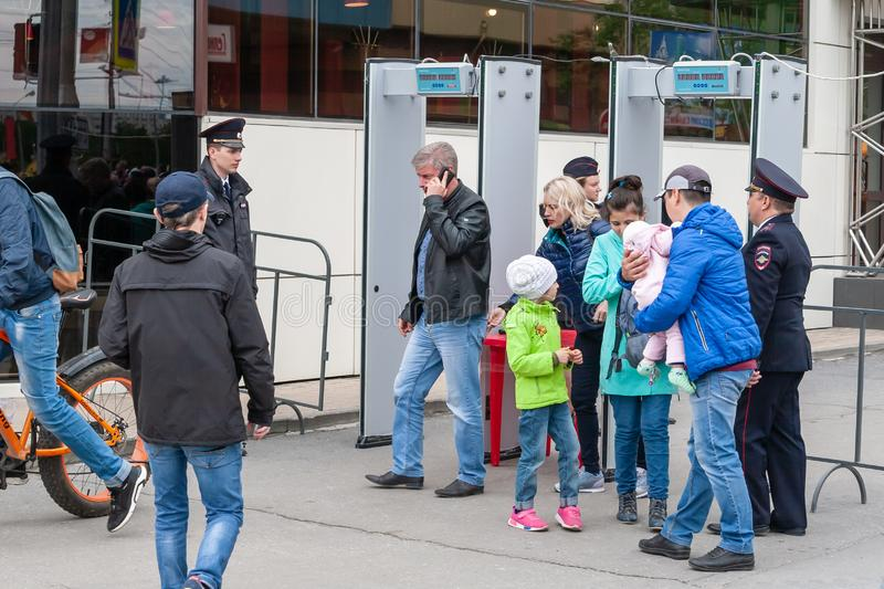 Police officers monitor the passage of citizens through the metal detector, before entering the festive event. Surgut, Russia, 06.12.2019: Police officers stock image