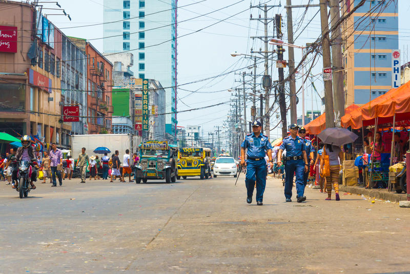 Police officers patrol street market in Manila, Philippines. Police officers patrol Divisoria Market in Manila, Philipppines. Divisoria is Manila's largest royalty free stock photography