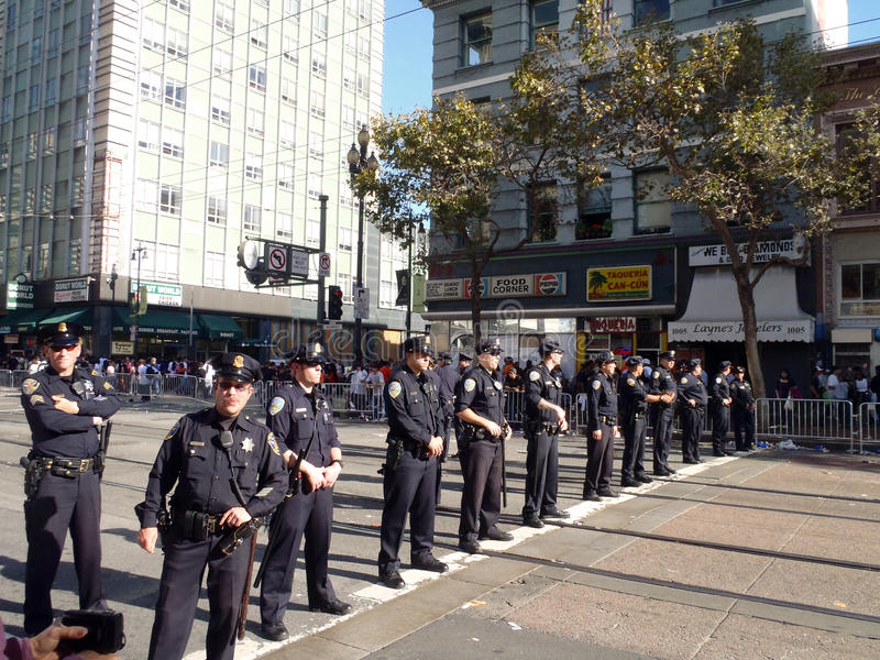 Police officers stand in line across market street