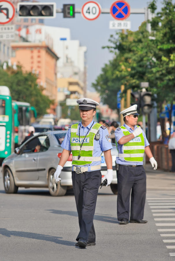 Police officers on the street during rush hour, Kunming, China. KUNMING-JULY 8, 2014. Police officers on the street during rush hour. Due to the rapid expansion royalty free stock image