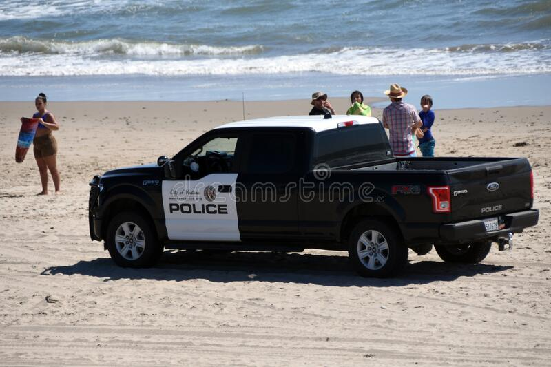 Covid-19 police patrol truck on the beach stock image
