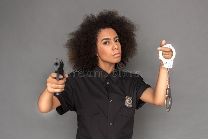 police Position de femme de mulâtre d'isolement sur la caméra de pointage grise avec l'arme à feu jugeant des menottes fraîches image stock