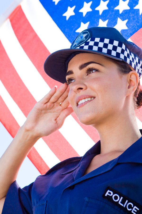 Police salute. Young american female police officer salute, background is USA flag royalty free stock images