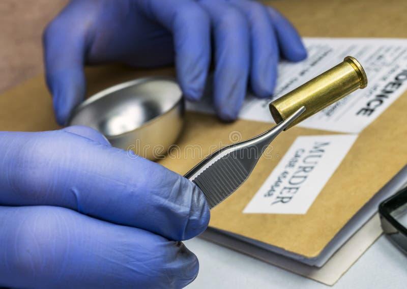 Police scientifique examinant un chapeau de balle dans le laboratoire ballistique image libre de droits
