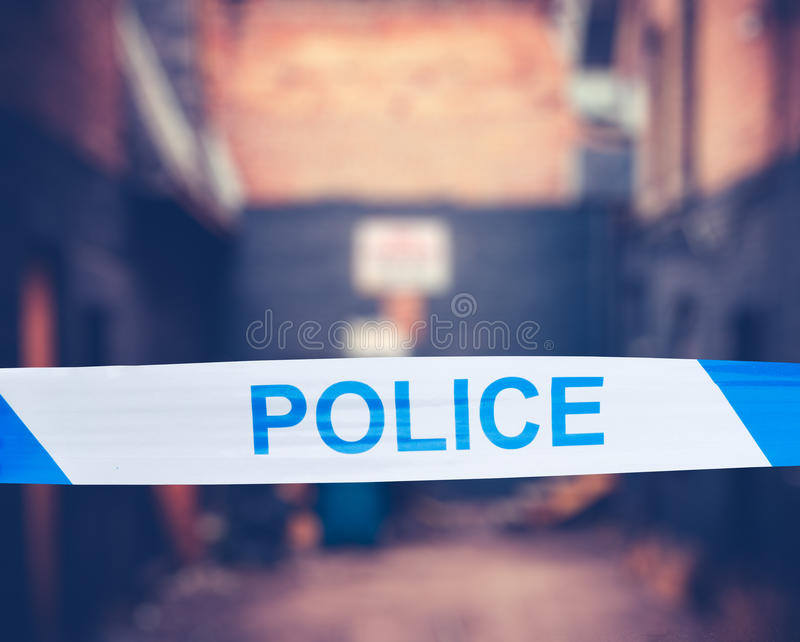 Police Tape In Urban Alley. British Police Tape Around A Crime Scene In A Grungy Urban Alley royalty free stock photo