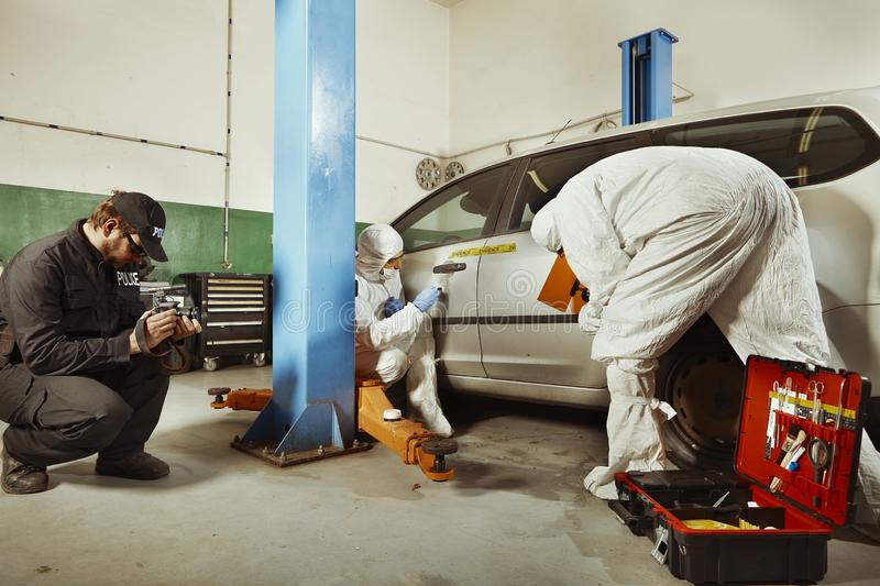 Police team working on traces collecting on confiscated car royalty free stock photo